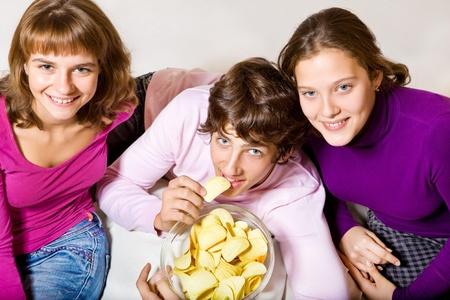 Cheerful teens eating crisps Stock Photo - 8372991
