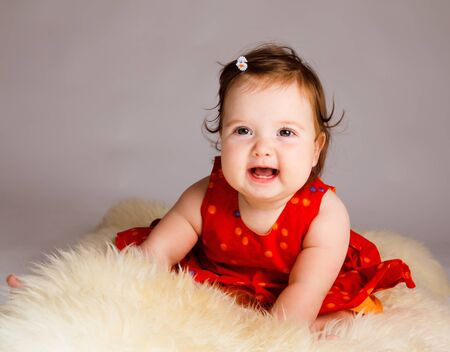 naughty or nice: Cheerful baby girl sitting on the sheepskin Stock Photo