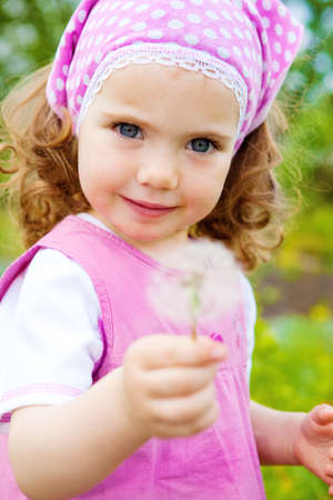 A sweet girl in the garden, with dandelion photo