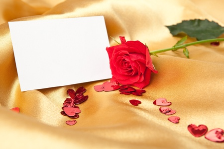 Blank greeting card and red rose on golden textile background