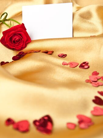 Red rose and white blank greeting card on golden satin photo