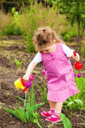 Cute curly girl watering tulips in the garden