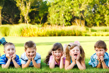 Five cute preschoolers laughing on the grass photo