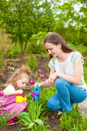 Woman with preschool girl watering flowers in  garden photo