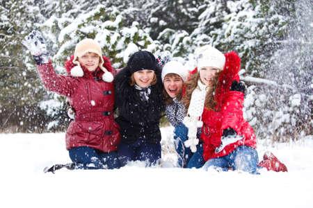Cute laughing teenage  friends throwing snow photo