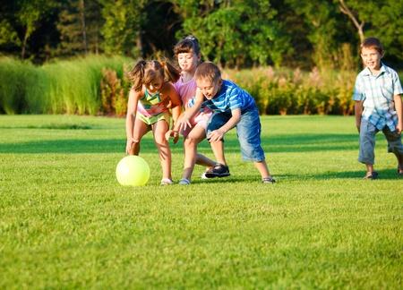ni�os jugando parque: Grupo de ni�os de edad preescolares felices atrapar el bal�n Foto de archivo