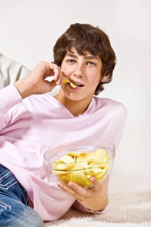 Portrait of a  hungry teenager eating crisps Stock Photo - 8590887