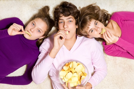 hungry children: Three teenage friends eating unhealthy crisps