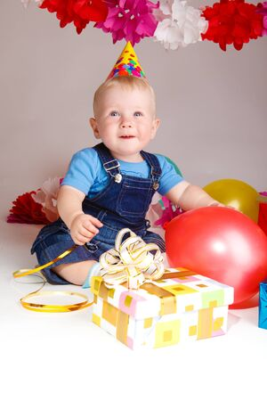 Cheerful infant in a party hat, sitting among balloons and presents photo