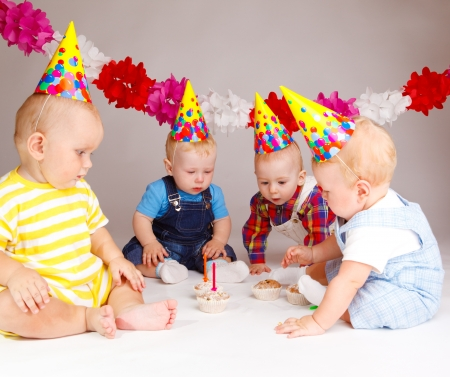 Group of babies looking at cupcakes with birthday candles photo
