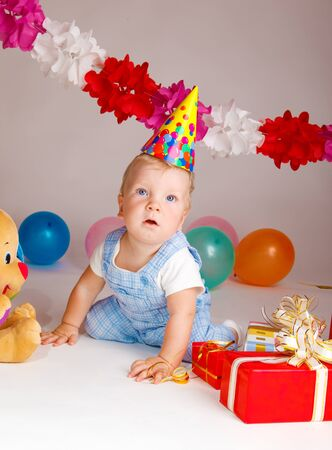 Baby in a party hat, looking surprised photo