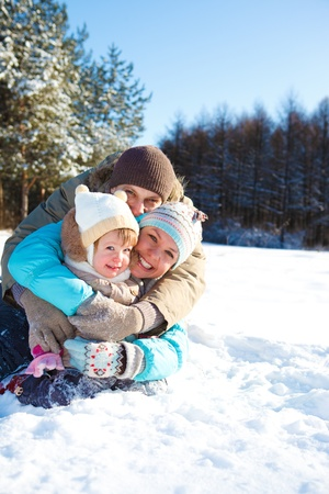 Cheerful loving family sit embracing in the winter park photo