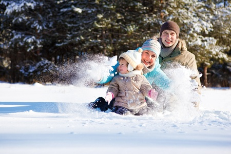 Attractive family having fun in fluffy snow photo