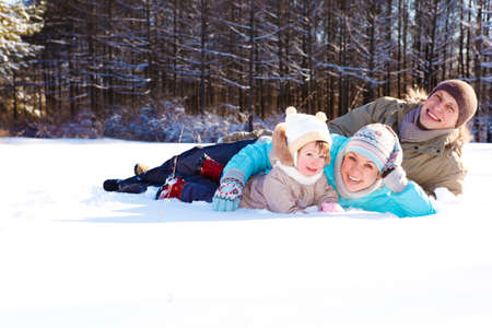 Attractive young parents and their daughter lying in snow photo