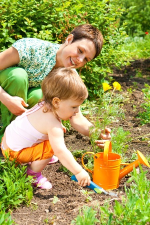 Mother and toddler daughters spring gardening