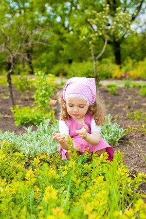 A sweet curly toddler girl in the garden