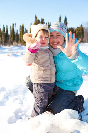 Woman and lovely toddler girl together in snow photo