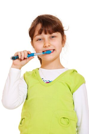Sweet preschool girl cleaning her teeth, isolated photo