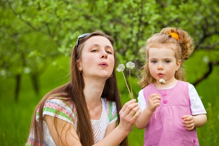 Mother and curly girl blowing dandelion away Stock Photo - 8797231