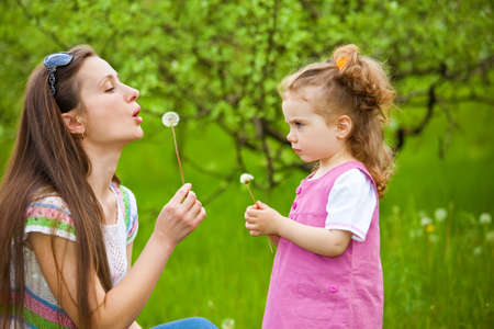 Mother and curly girl blowing dandelion away photo