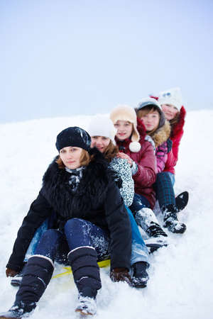 Group of teenage girls sledging from the hill photo