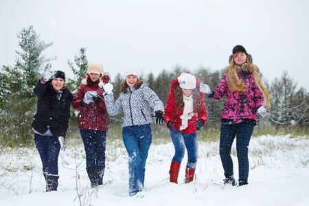 Teenagers playing snowballs in a winter park photo