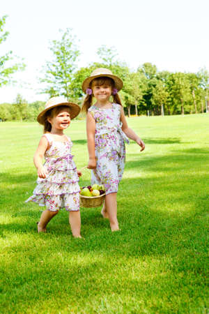 Two sweet kids carrying  basket with fruit photo