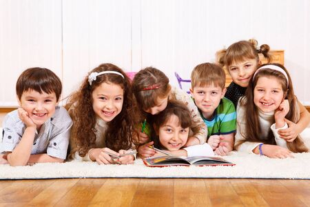 Cheerful kids crowd reading  a book Stock Photo - 8797286