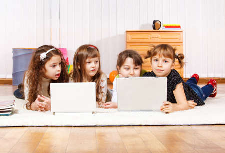 Four little friends lying on the floor with laptops photo