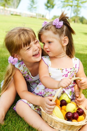 Laughing kids sit with fruit basket in the garden Stock Photo - 8797154