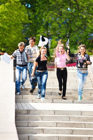 successful student: Excited college students running down the stairway and throwing books up Stock Photo