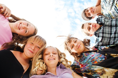 Company of excited teens hugging Stock Photo