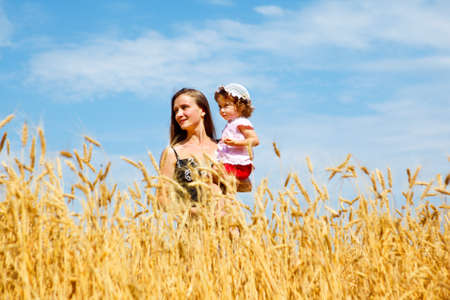 Mother holding her lovely daughter in wheat photo