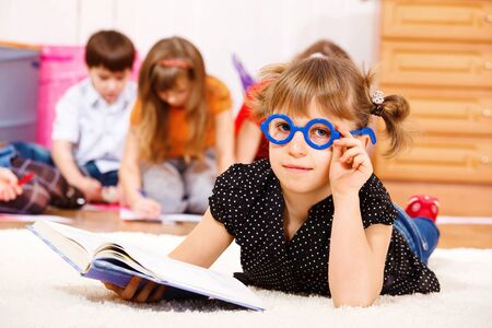 Lovely girl in glasses lying with book in hands Stock Photo - 8801312