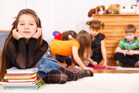 Attractive junior school student lying on the books stack Stock Photo - 8797298