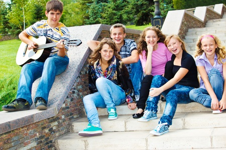 teens playing: Cheerful teenagers sitting on the stairway