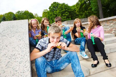 outdoor eating: High school students with fast food