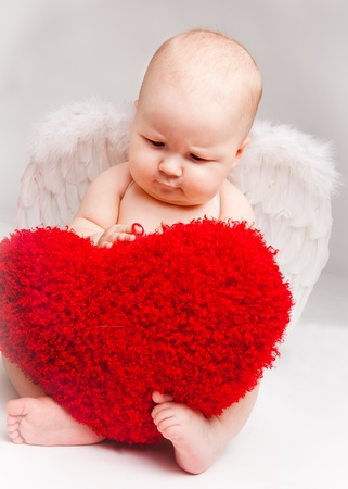 Baby angel playing with red heart, over gray Stock Photo - 8797329