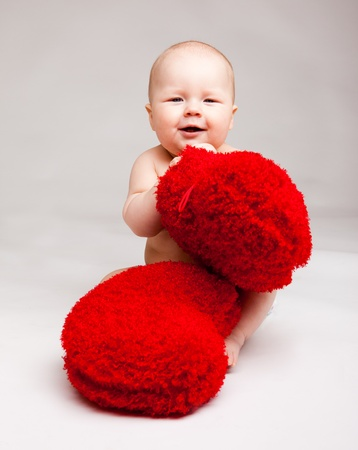 Cute happy valentine baby playing with red heart shaped pillows photo