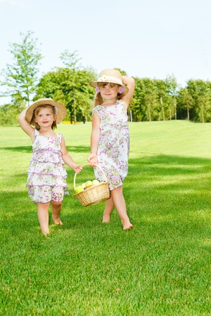 Little girls in straw hats carrying  fruit basket  photo