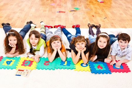 Six elementary school students with puzzled numbers photo