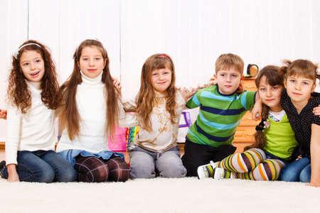 Six kids sit embracing Stock Photo - 8797241