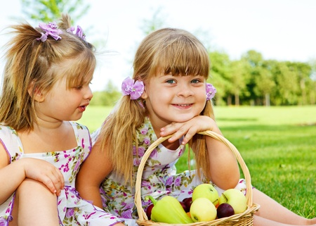 Two sweet kids in garden with fruit basket beside photo