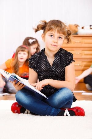 Girl sitting with book in hands photo