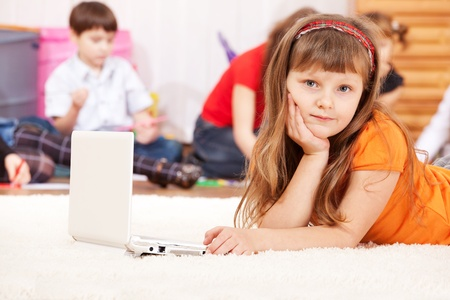 Girl lying on the floor with laptop beside photo