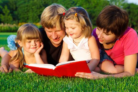 Lovely family reading a book on the  grass photo