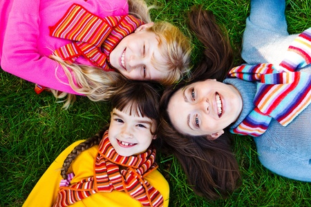 Mother and two girls in bright scarves lying on the grass photo