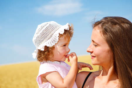 Portrait of woman and curly toddler girl in the outdoor photo
