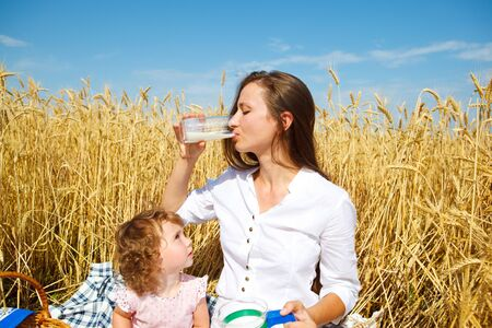 Woman drinking milk in wheat field, curly daughter looking at her photo