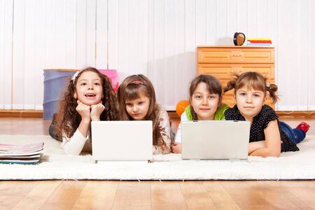 Four little friends with two laptops photo